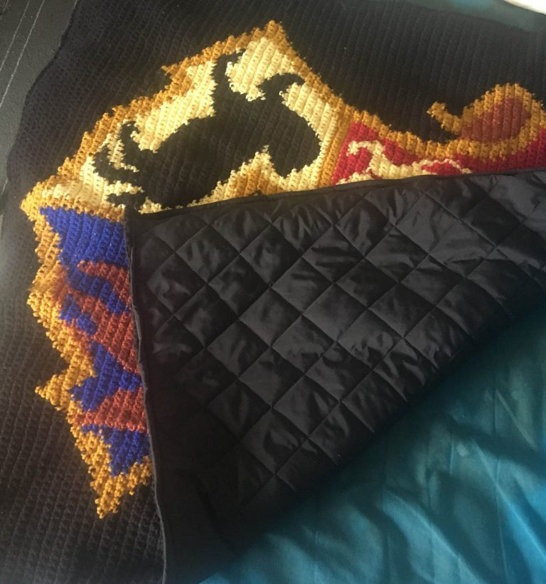 back view of crochet blanket depicting the Hogwarts crest from Harry Potter, showing the quilted backing