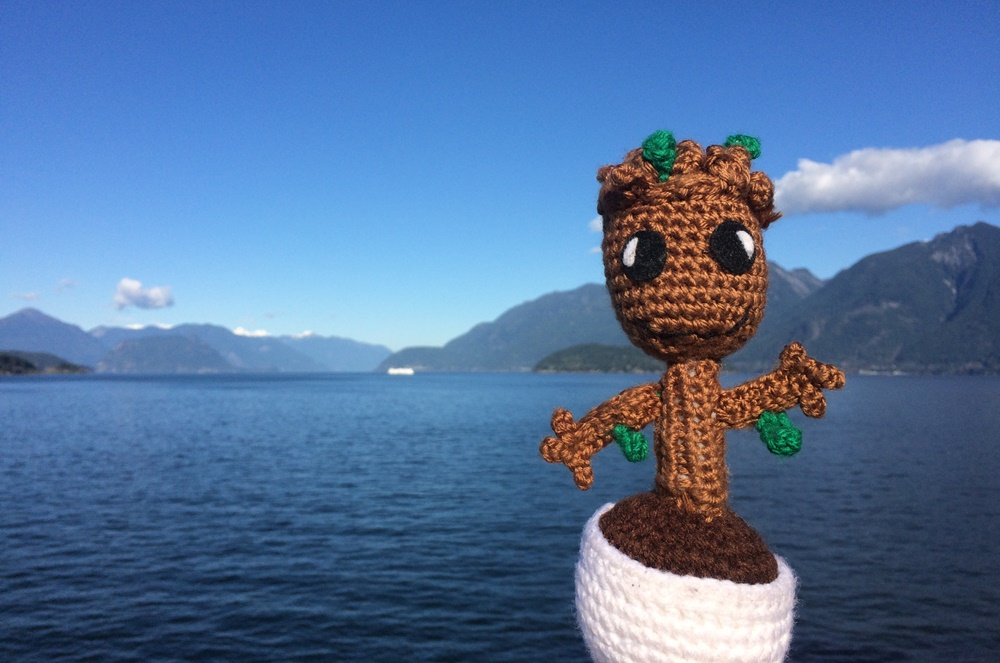 a crochet baby groot doll held up in front of an ocean and mountain background