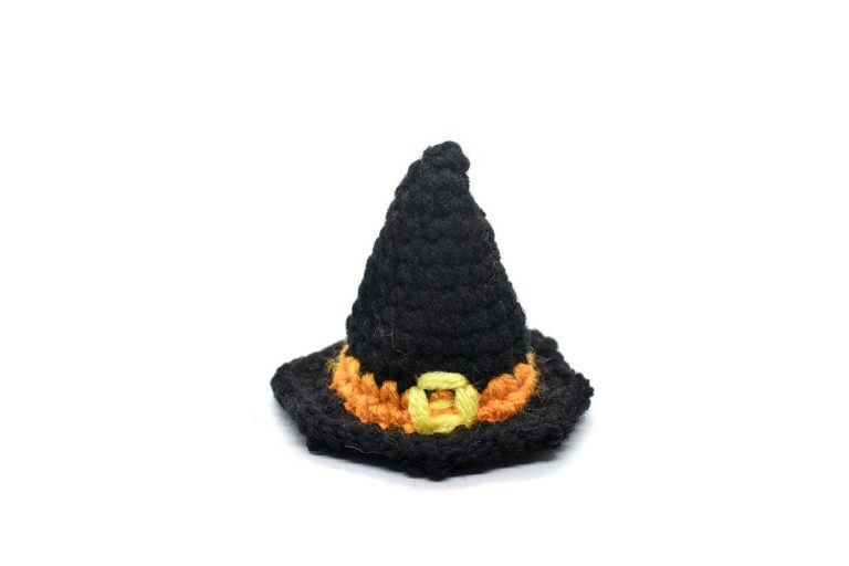 a small crocheted black witch hat with an orange band and a yellow buckle