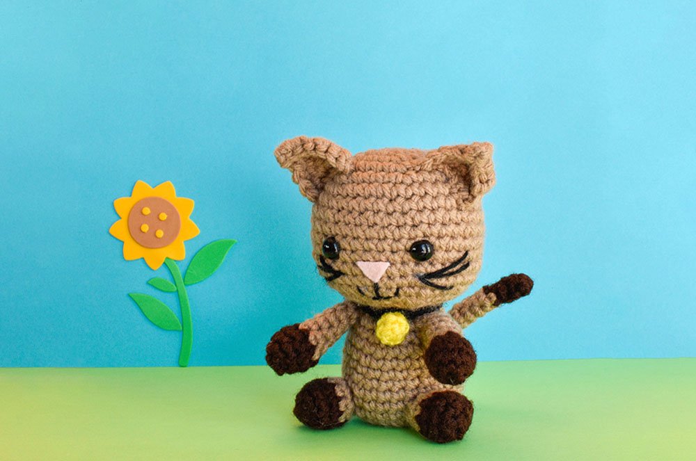 a crochet kitten doll against a blue and green backdrop