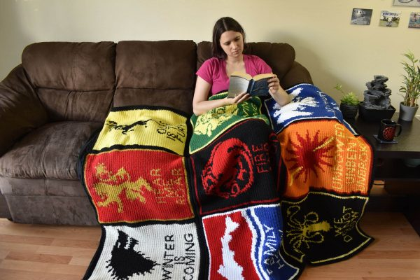 a woman sitting on a couch reading, with a game of thrones crochet blanket across her lap
