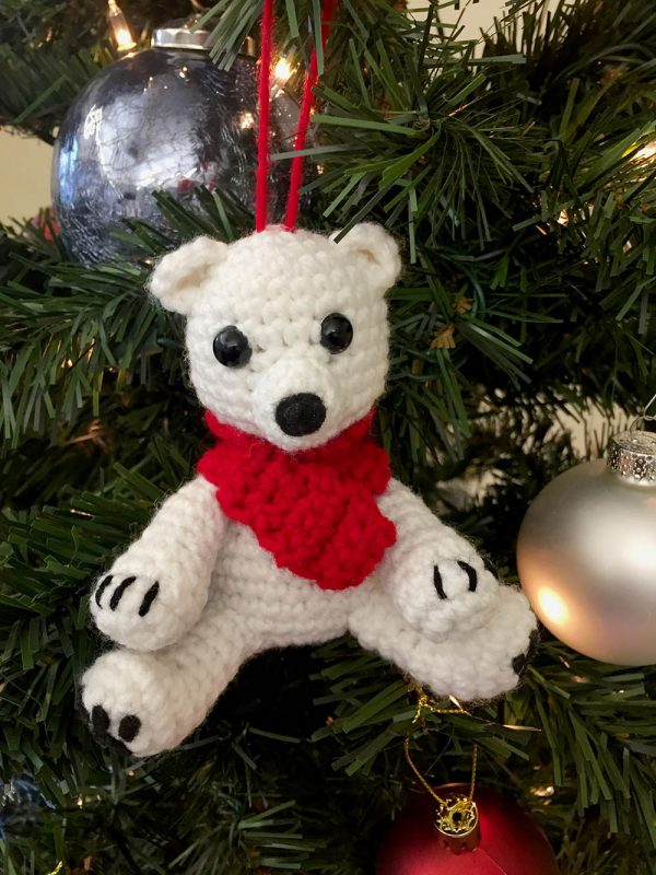 crochet polar bear ornament wearing a red scarf and hanging from a christmas tree