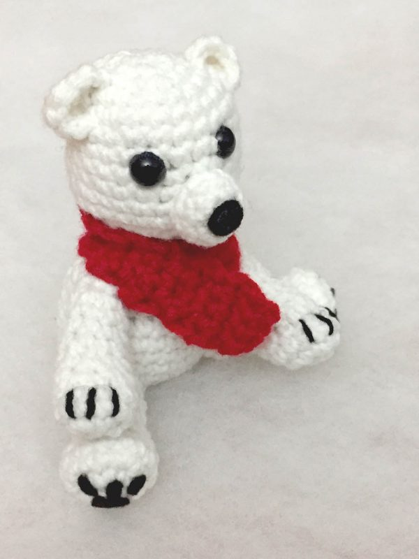 side view of crochet polar bear wearing a red scarf