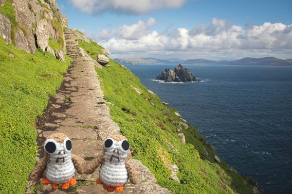two crochet porg dolls photoshopped against a background of ahch-to island from star wars