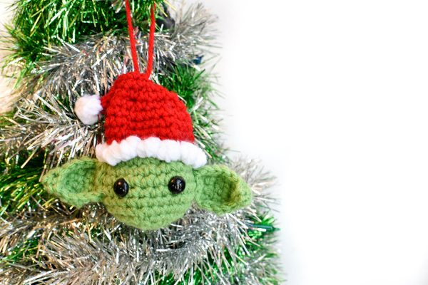 crochet christmas ornament of yoda wearing a santa hat and hanging from a christmas tree