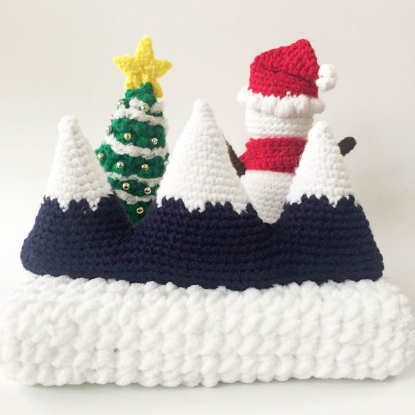 back view of diorama of a crochet snowman with a crochet christmas tree and crochet mountains