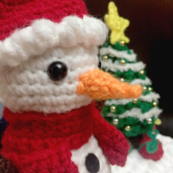 crochet snowman with a santa hat and red scarf, and a christmas tree in the background
