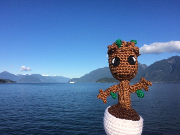 baby groot crochet doll in front of an ocean and islands landscape