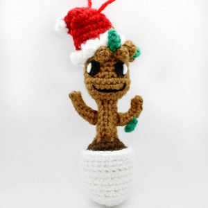 crochet orgnament of baby groot wearing a santa hat