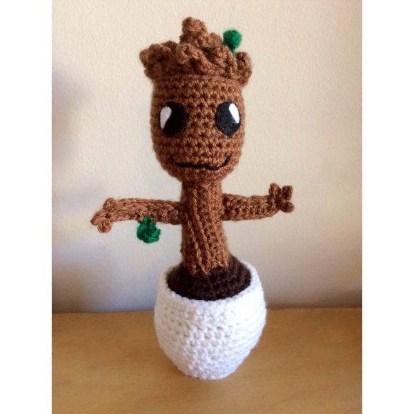 crochet baby groot doll standing on a table