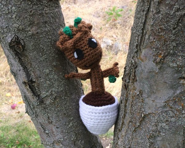 baby groot crochet doll perched in a tree