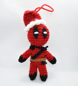 crochet ornament of deadpool wearing a santa hat