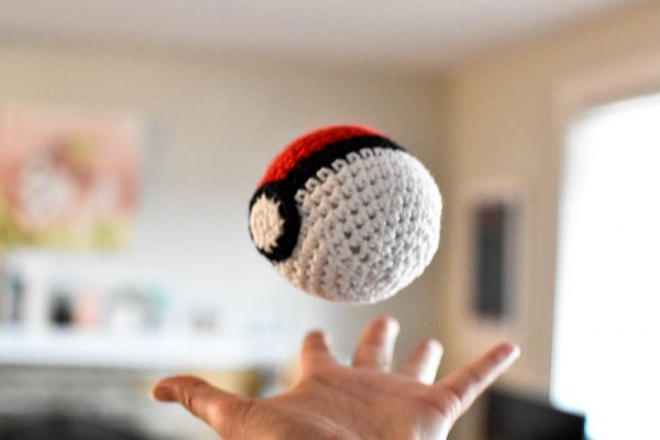 pokeball amigurumi toy being thrown in the air in a living room