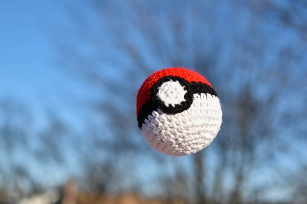 pokeball amigurumi toy being thrown in the air outside