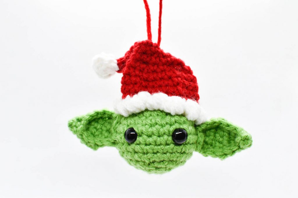 crochet christmas ornament of yoda wearing a santa hat