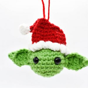 crochet christmas ornament of yoda wearing a santa hat