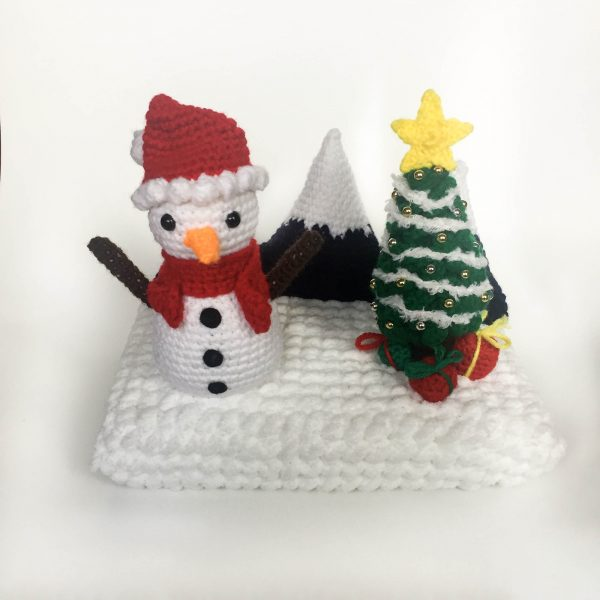 diorama of a crochet snowman with a crochet christmas tree and crochet mountains