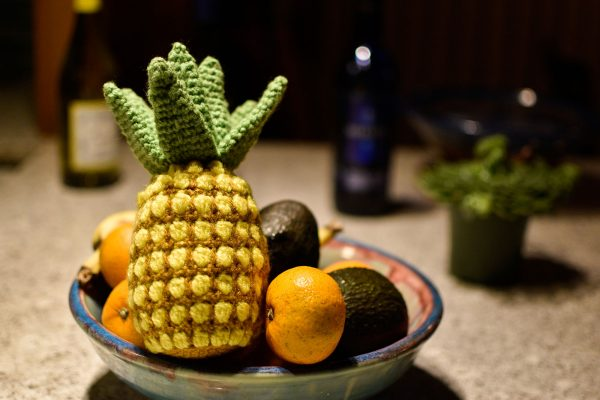a crochet pineapple sitting in a bowl of real fruit