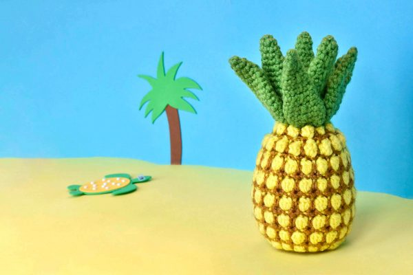 crochet pineapple against a yellow and blue fake beach backdrop with a cartoon palm tree and turtle