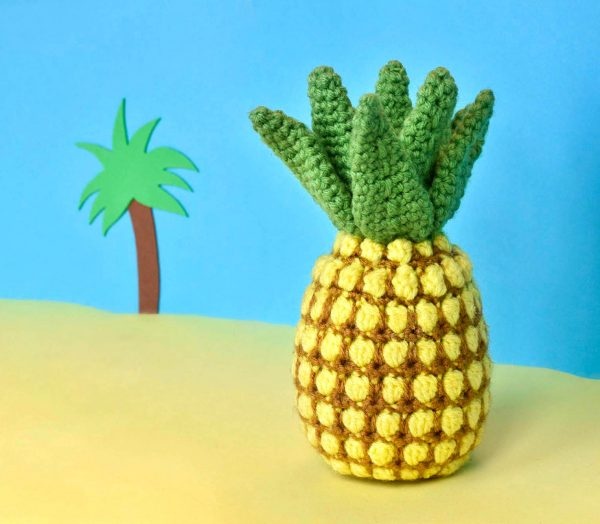 crochet pineapple against a yellow and blue fake beach backdrop with a cartoon palm tree