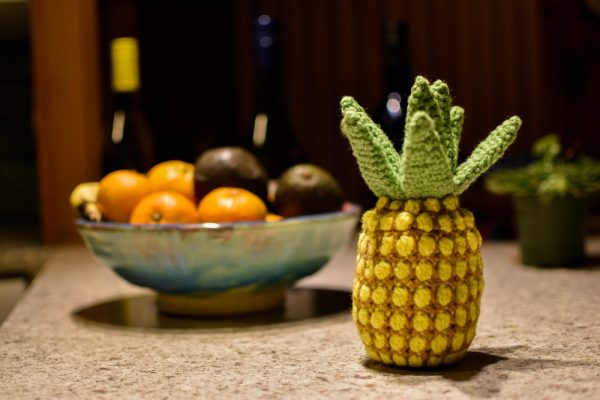 a crochet pineapple displayed on a counter next to a bowl of real fruit