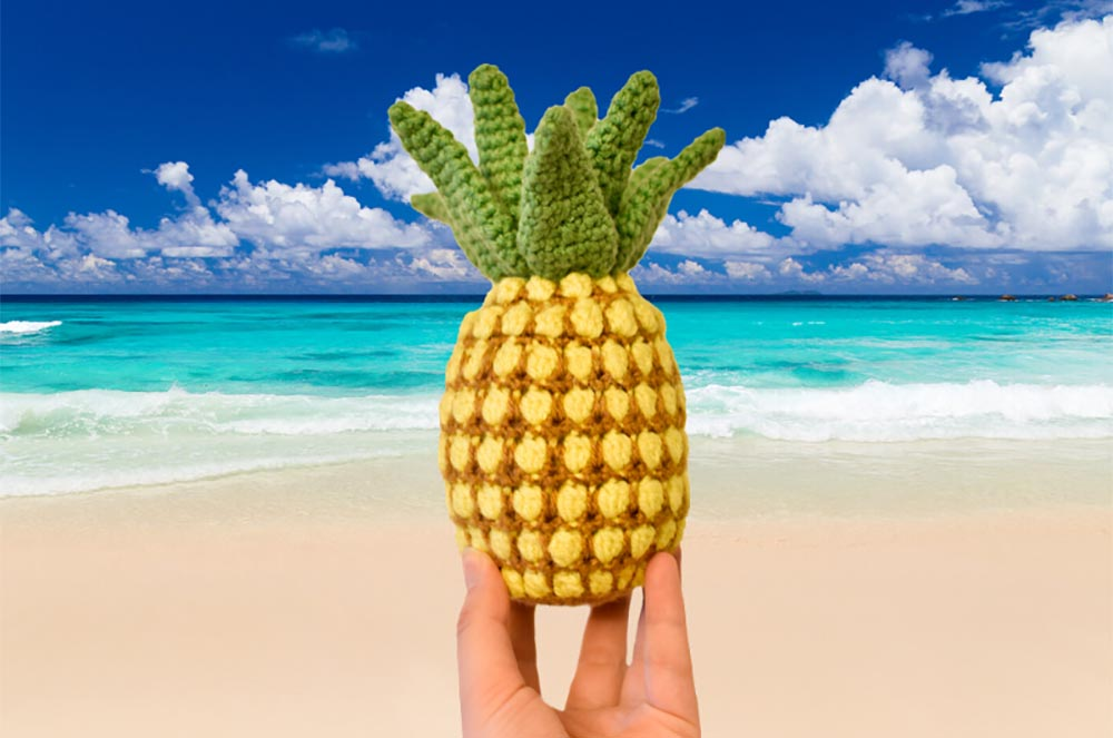 a crochet pineapple with a tropical beach in the background