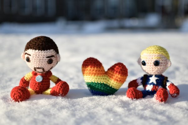 picture of crochet iron man and captain america dolls sitting in the snow with a crochet pride flag heart between them