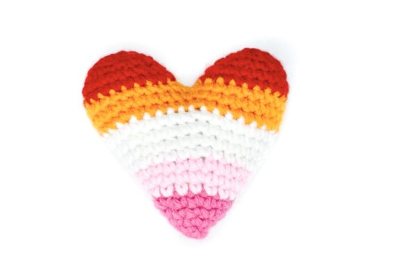 crochet heart in the colours of the lesbian flag: red, orange, white, light pink, and pink
