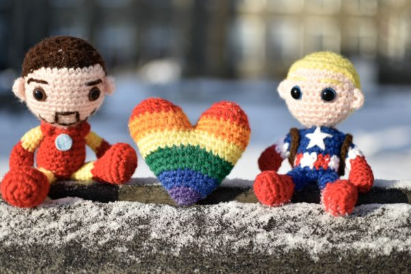 picture of crochet iron man and captain america dolls with a crochet pride flag heart between them