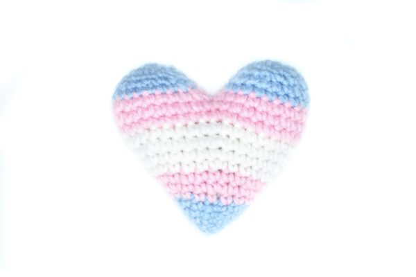 crochet heart in the colours of the trans flag: light blue, light pink, and white