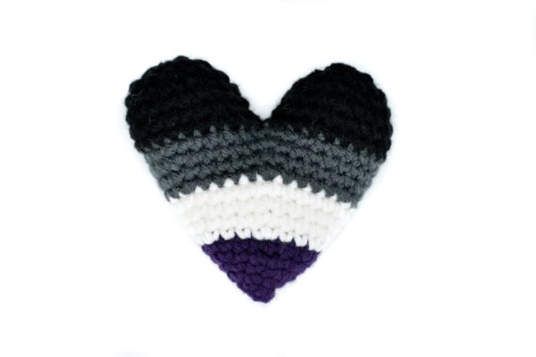 crochet heart in the colours of the asexual flag: black, grey, white, and purple