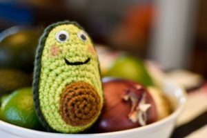 a crochet avocado sitting in a bowl with some real fruits and vegetables