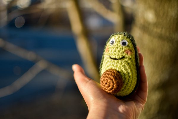 crochet avocado doll held up in front of a tree