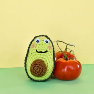 crochet avocado doll next to some real tomatoes