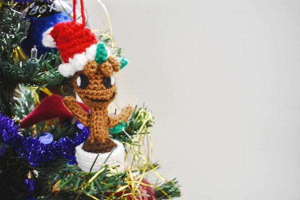 crochet baby groot christmas ornament doll hanging from a christmas tree