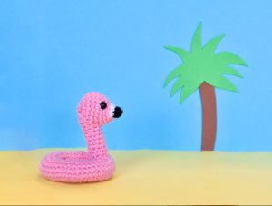 a small crochet flamingo floatie with a colourful cartoon style beach backdrop