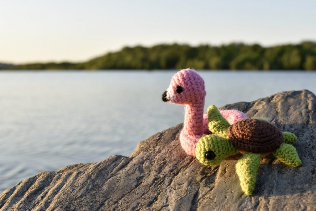 a crochet flamingo and a crochet turtle sitting on a rock overlooking a lake in the evening