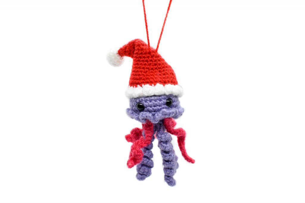 a small crochet jellyfish wearing a Santa hat