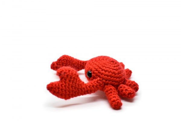 Side view of a small crochet crab against a white background