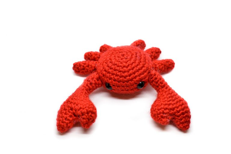 Front view of a small crochet crab against a white background
