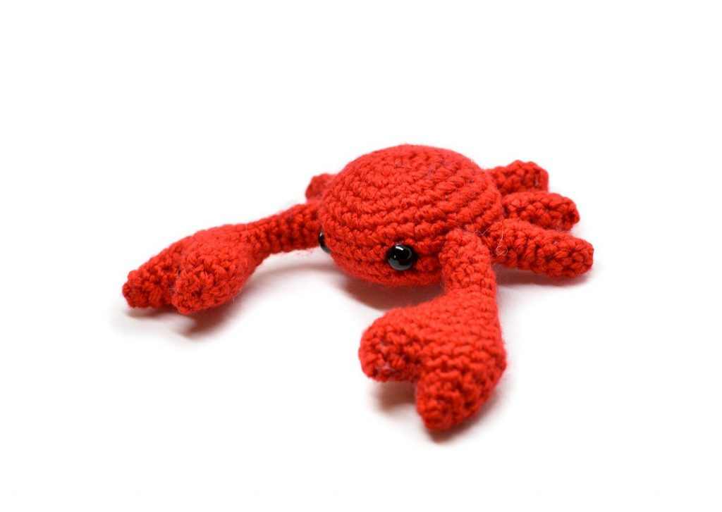 a small crochet crab against a white background