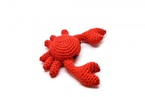 Side top view of a small crochet crab against a white background