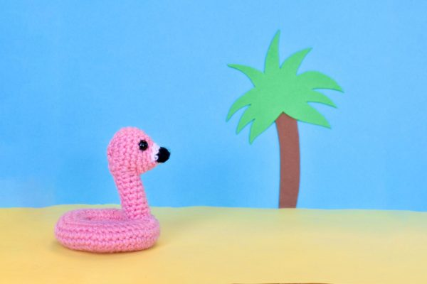 a small crochet flamingo floatie toy against a fake tropical beach backdrop made out of construction paper