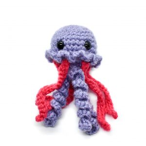 a small crochet purple and pink jellyfish toy against a white background