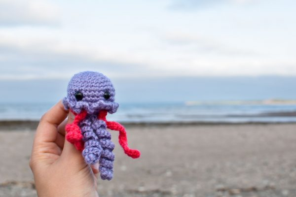 a small crochet purple and pink jellyfish toy held up in front of an ocean beach