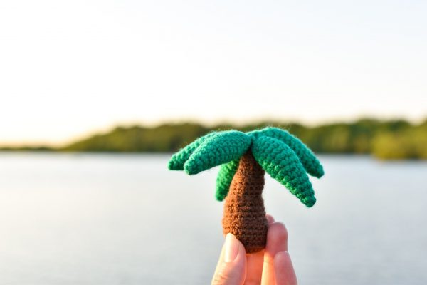 a small crochet palm tree toy held up in front of a lake