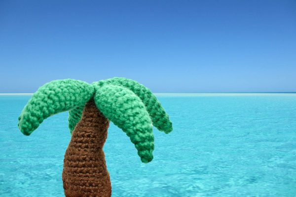 a small crochet palm tree toy shown photoshopped against a tropical ocean background