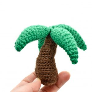 a small crochet palm tree toy held up against a white background