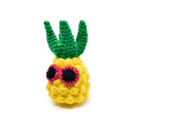 a small crochet pineapple toy with pink sunglasses against a white background
