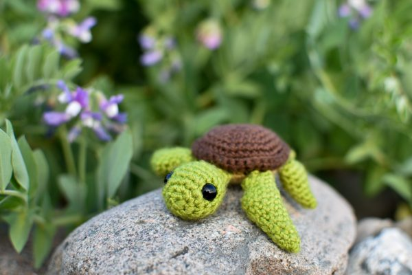 a small crochet sea turtle toy sitting on a rock with a background of green leaves and purple flowers